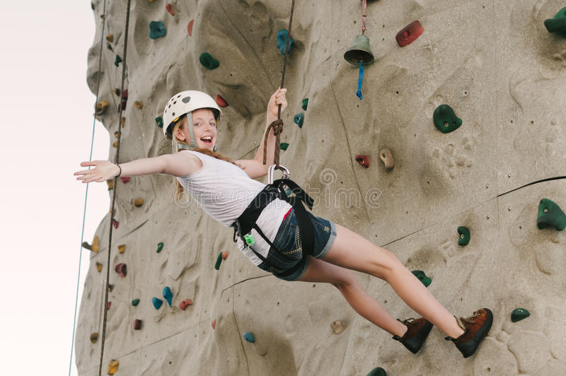 A teen girl climbing on a rock wall leaning back against the rope. stock photography