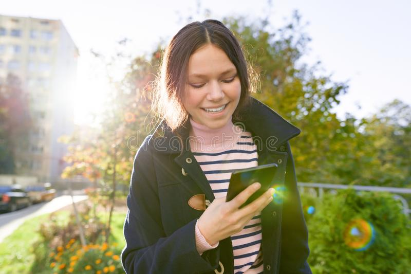 Teen girl in coat using smartphone, sunny autumn day stock photography