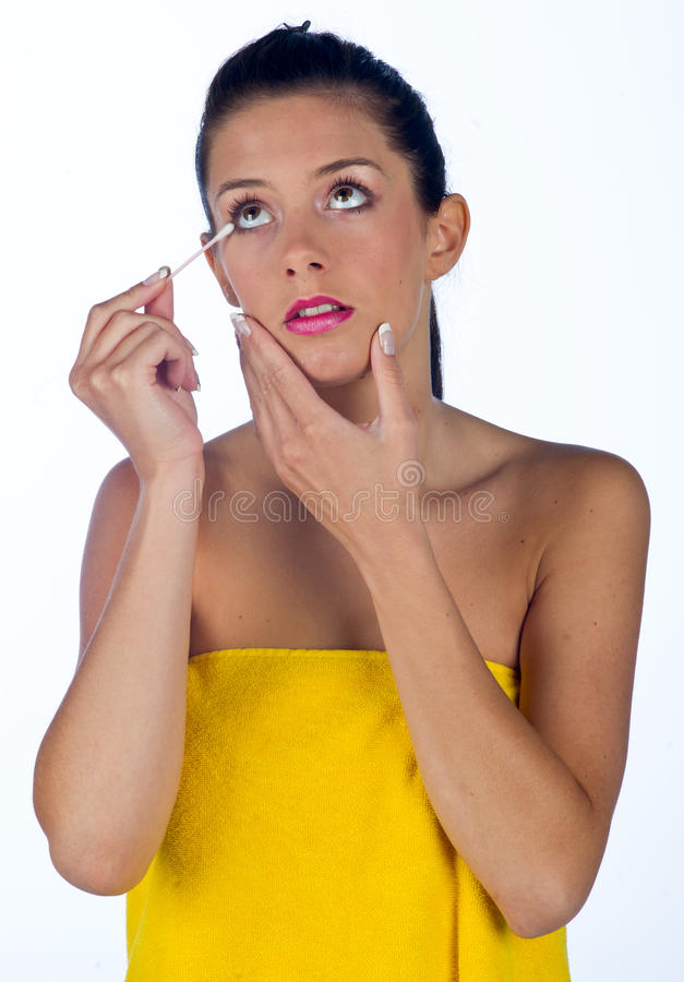 Teen girl with cotton stick. Teen girl cleaning her eye with cotton stick royalty free stock photography