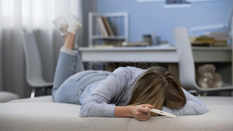 Teen girl crying because of early pregnancy, feeling desperate, unwanted baby. Stock photo stock photos