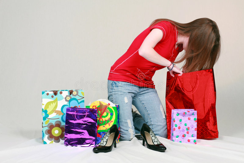 Teen girl digging in shopping bags royalty free stock photos