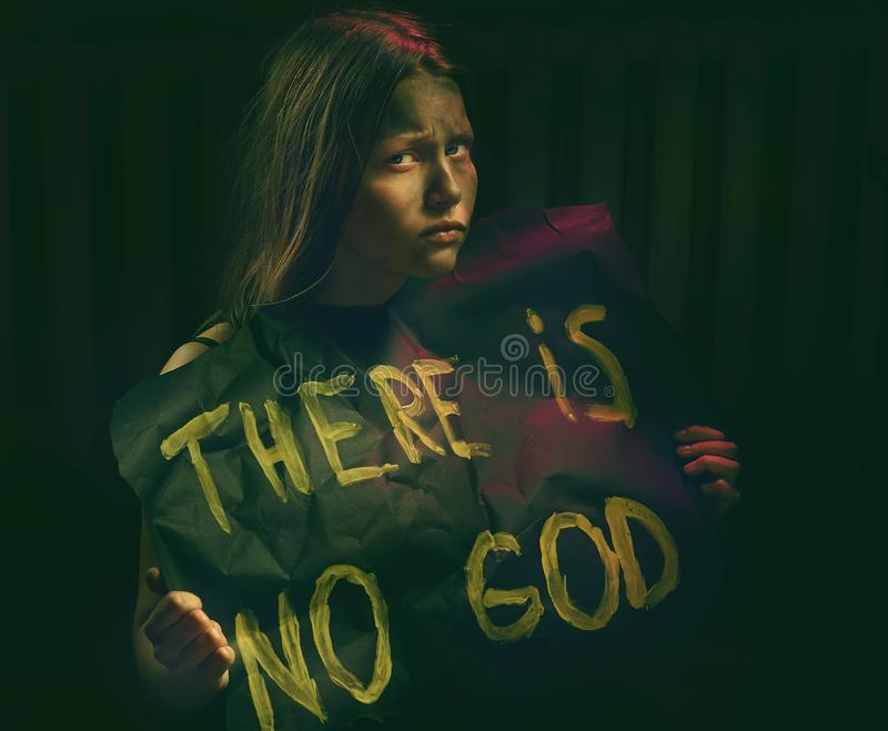 Teen girl with dirty face holding banner with a text - There is no God. royalty free stock image
