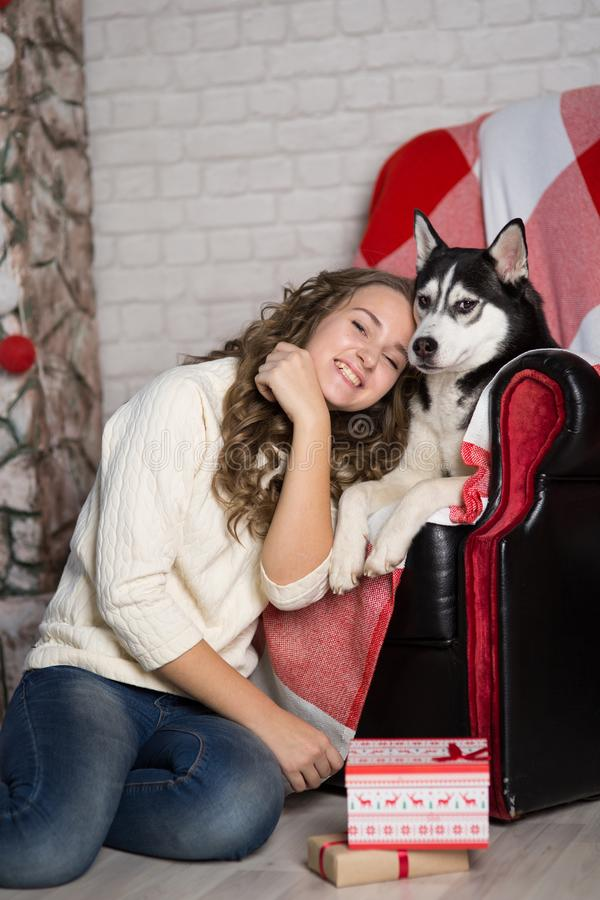 Teen girl with dog in a room for Christmas royalty free stock photo