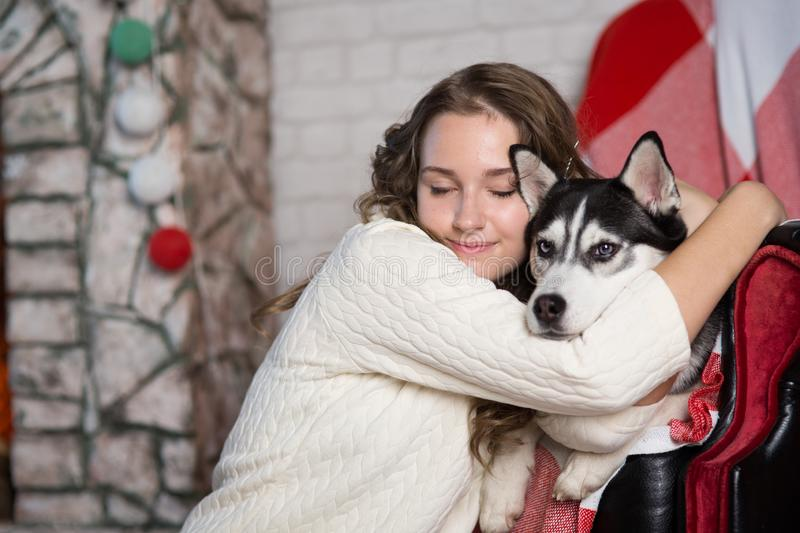 Teen girl with dog in a room for Christmas royalty free stock photography