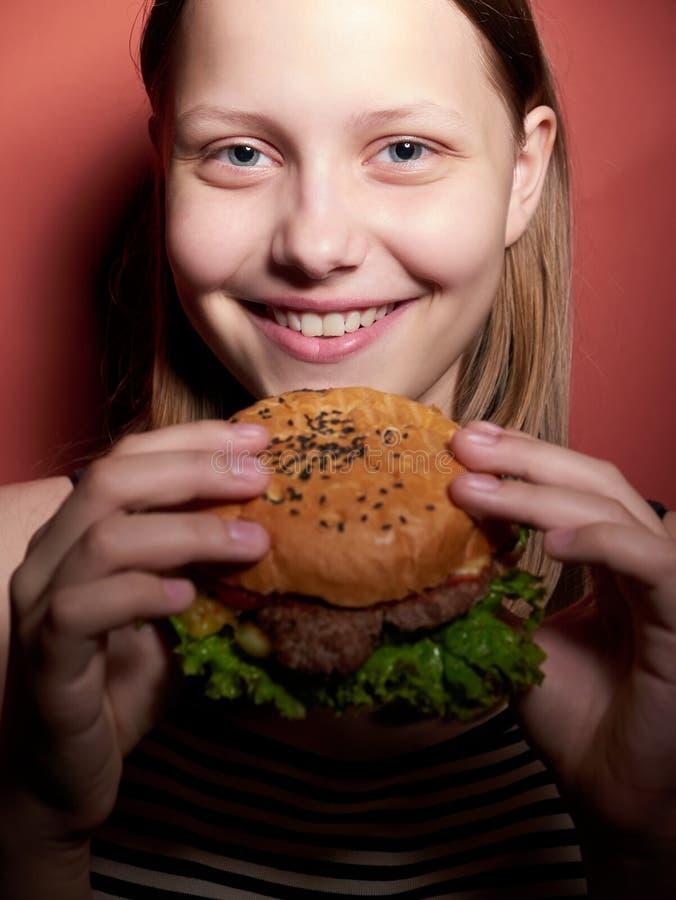 Teen girl eating a burger stock images