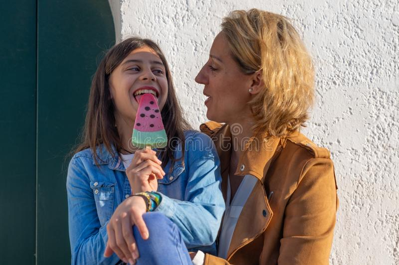 Teen girl eating a watermelon ice cream next to her mother in coastal town of Europe stock photography