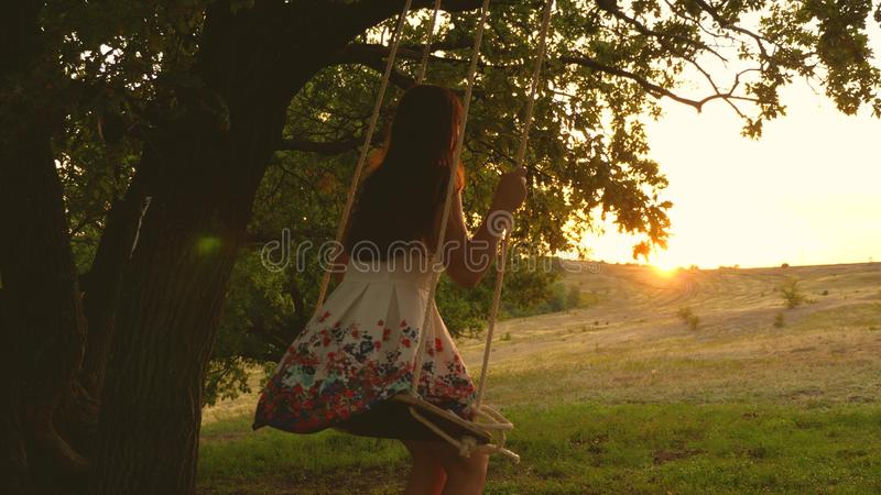 Teen girl enjoys a flight on a swing on a summer evening in the forest. young girl swinging on a rope swing on an oak. Teen girl enjoys a flight on a swing on a royalty free stock photos