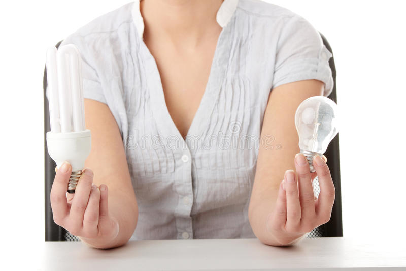 Teen girl environmentalist comparing bulbs. Teen girl environmentalist comparing one compact fluorescent light bulb to incandescent light bulb royalty free stock photos