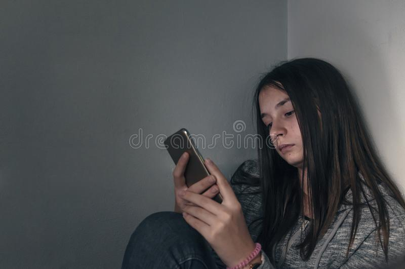 Sad teen checking phone sitting on the floor in the living room stock photography