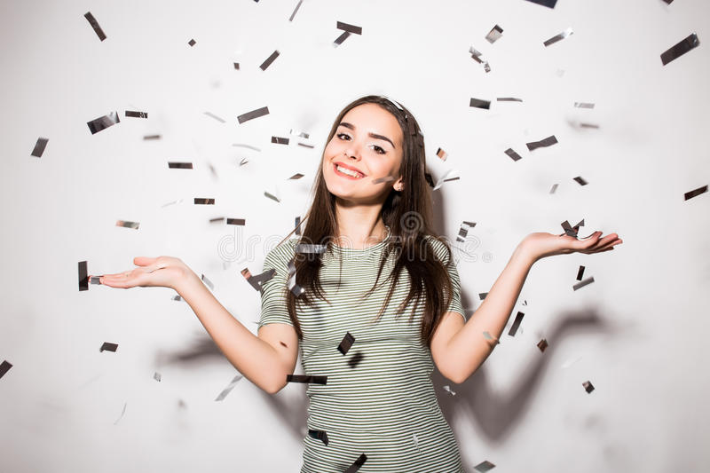 Teen girl in fancy dress with sequins and confetti at party. Happy young woman or teen girl in fancy dress with sequins and confetti at party on grey background royalty free stock images