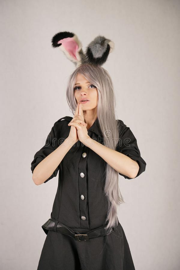 Teen girl in FBI black carnival dress with big fur rabbit ears loves cosplay and stands on white Studio background royalty free stock photo