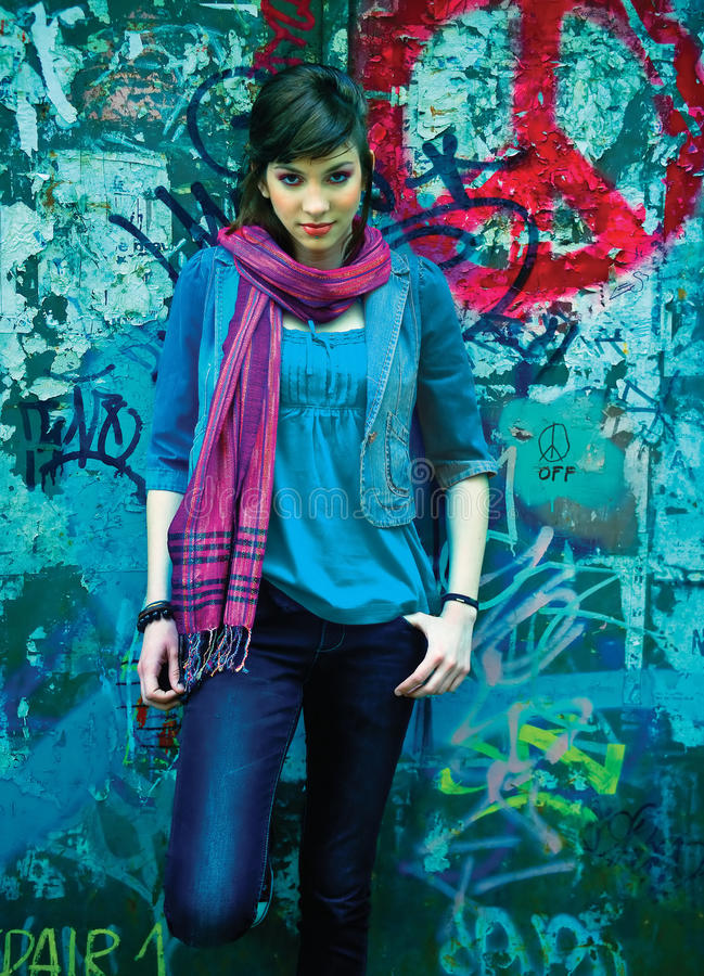 Teen girl in front of peace sign. Graffiti stock image