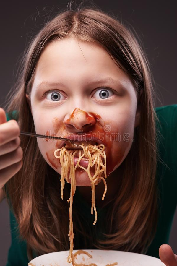 Teen girl furiously eating. Her food with ketchup on her face royalty free stock image