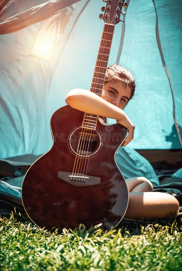 Teen girl with guitar. Nice teenager girl sitting on the fresh green grass with guitar, talented child plays a musical instrument, enjoying active time at summer royalty free stock image