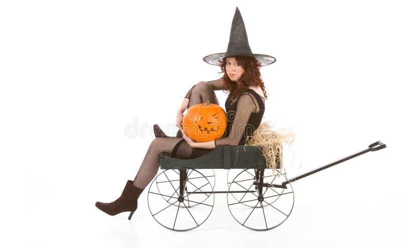 Teen girl in Halloween costume on cart by pumpkin stock photography