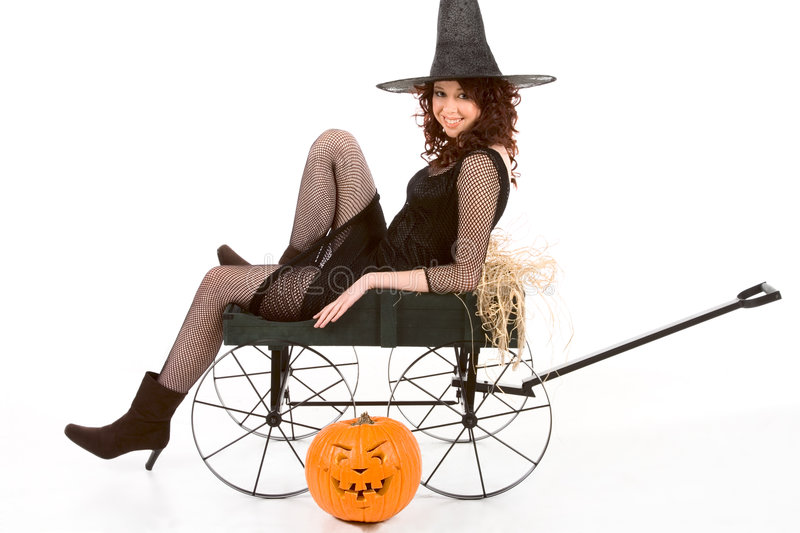 Teen girl in Halloween costume on cart by pumpkin royalty free stock photography
