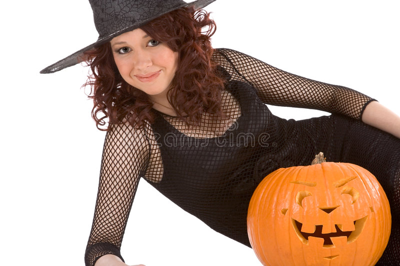 Teen girl in Halloween hat with carved pumpkin stock photos