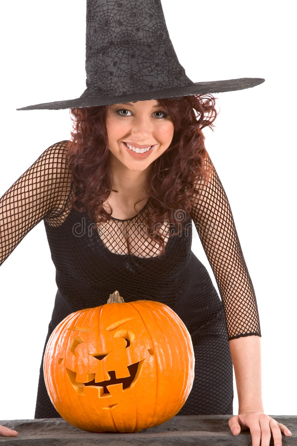 Teen girl in Halloween hat with carved pumpkin stock photography