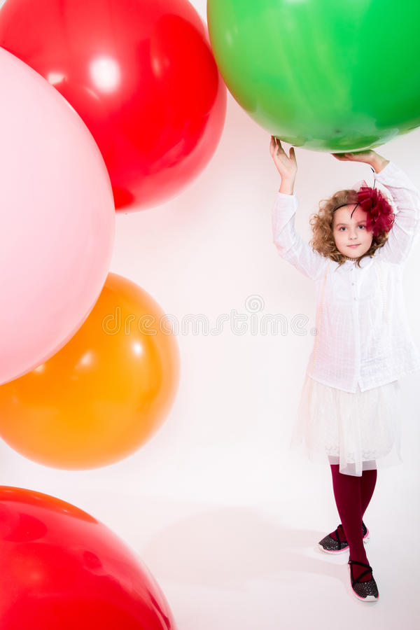 Teen girl in a hat and white dress on a background of big colored rubber air balls stock photos