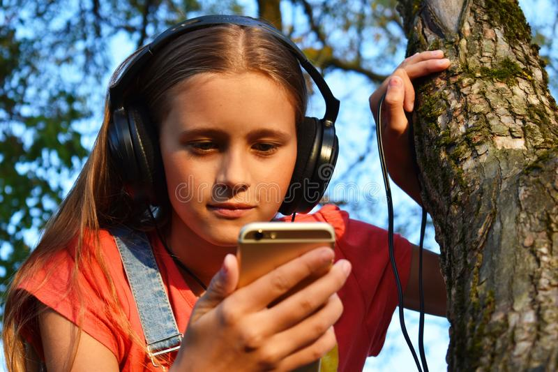 Teen girl in headphones looks at phone royalty free stock photos