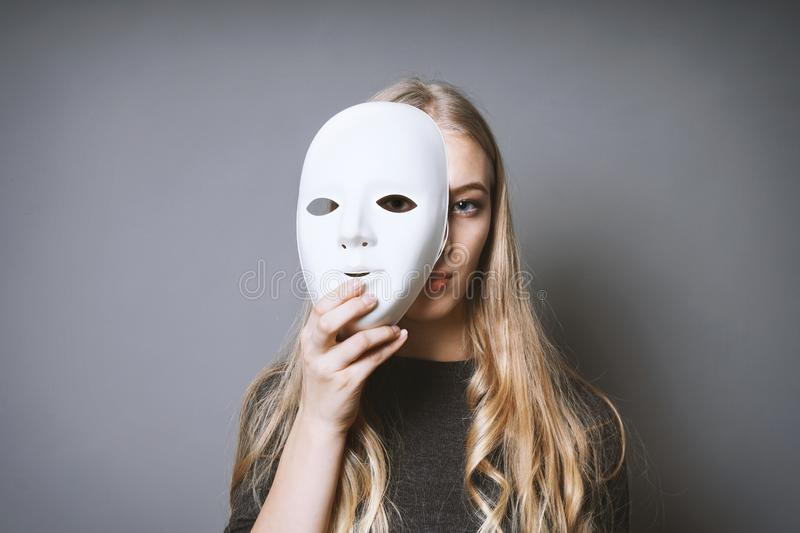 Teen girl hiding face behind mask royalty free stock images