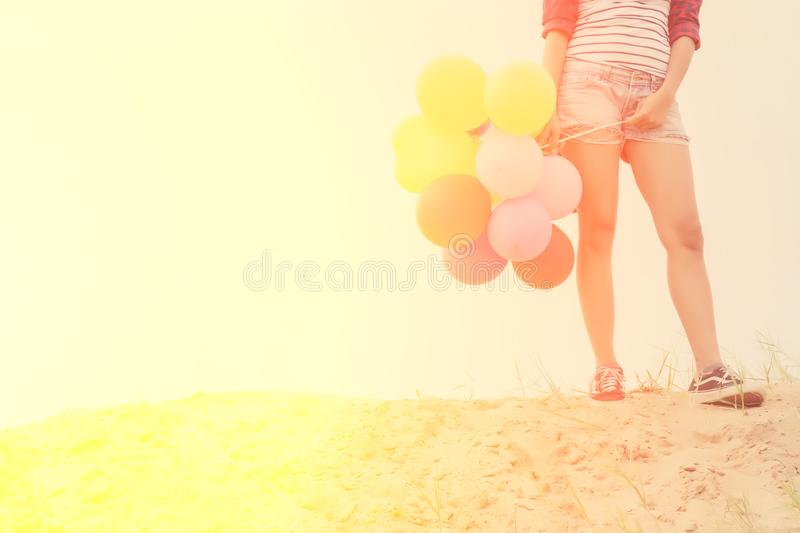 Teen girl holding colorful balloons on the sand. royalty free stock photos