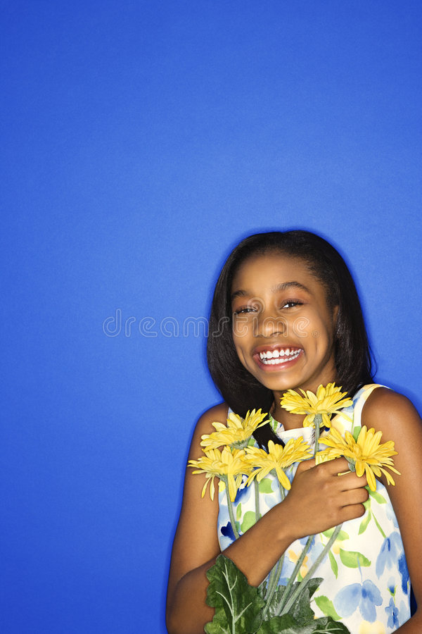 Teen girl holding flowers. Portrait of African-American teen girl holding a bouquet of daisies and smiling against blue background royalty free stock images