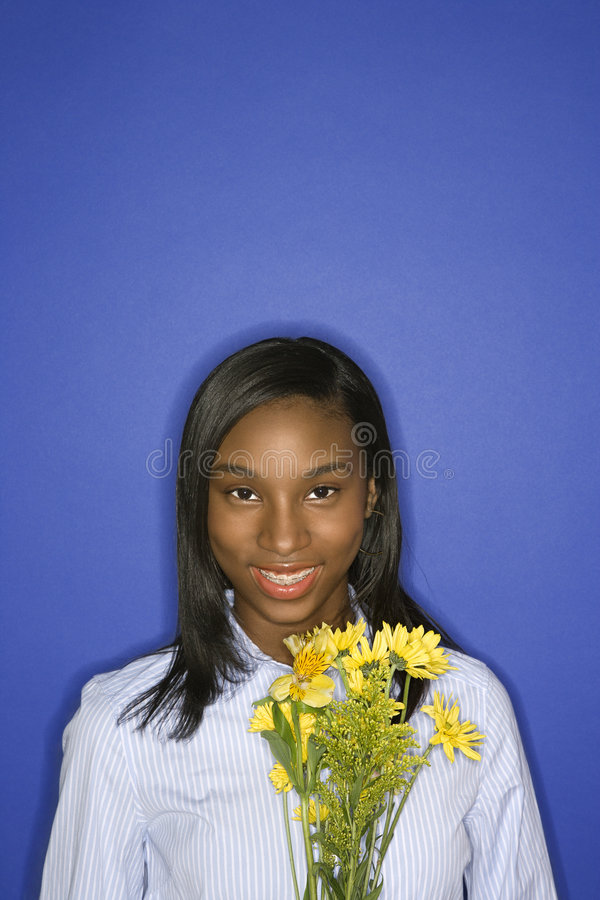 Teen girl holding flowers. Portrait of smiling African-American teen girl with bouquet of yellow flowers in front of blue background stock photography