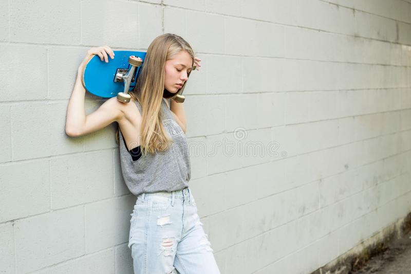 Teen girl holding her skateboard against a wall. royalty free stock photography