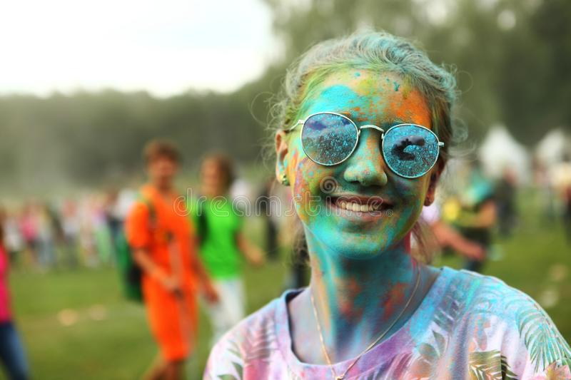 Teen girl on holi fest. MOSCOW - SEPTEMBER 6, 2014: Unidentified girl smiles during the Color Fest on September 2014 in Moscow, Russia. Roots of this fest are in stock image