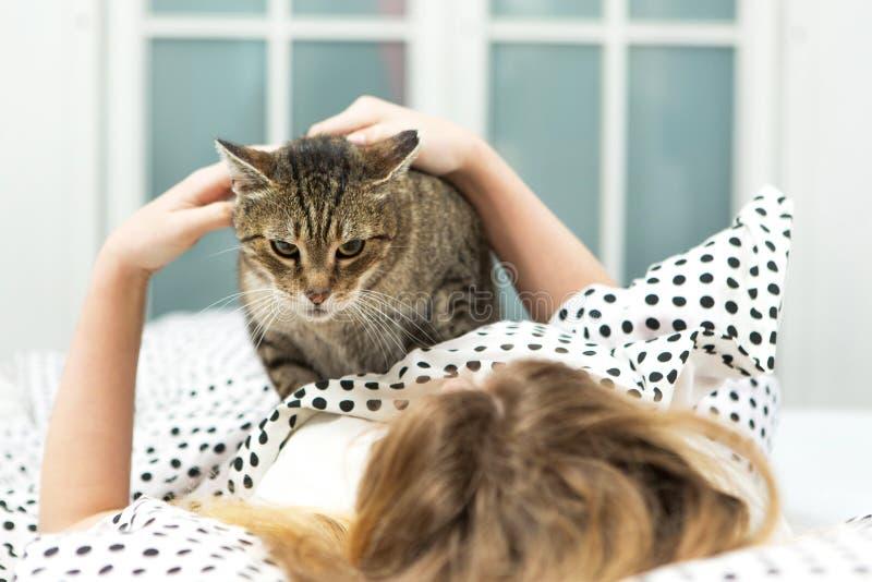 Teen girl hug cat in bed,. Girl and her Pet Cat stock image