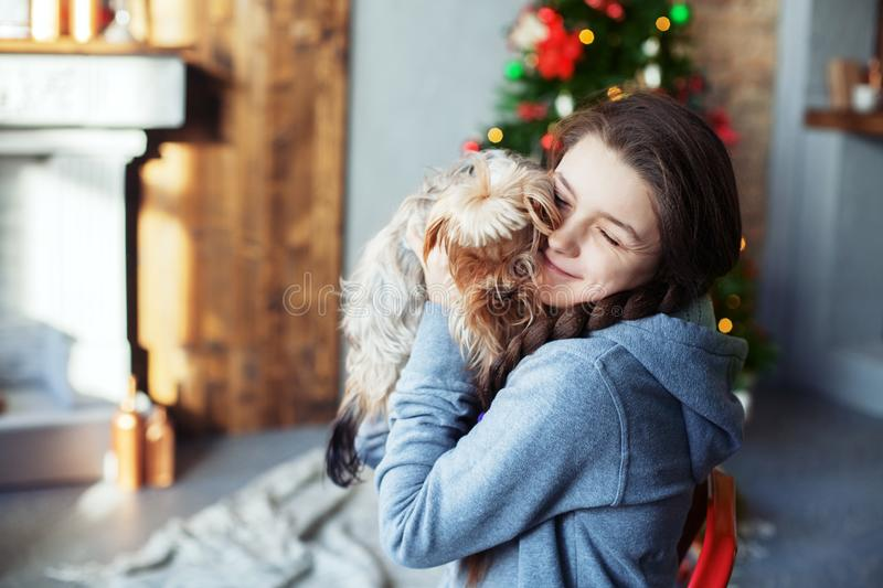 Teen girl hugging a dog. The concept of Christmas stock photos