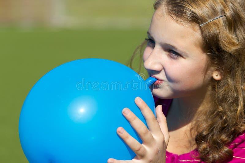 Teen girl inflates the balloon royalty free stock photo
