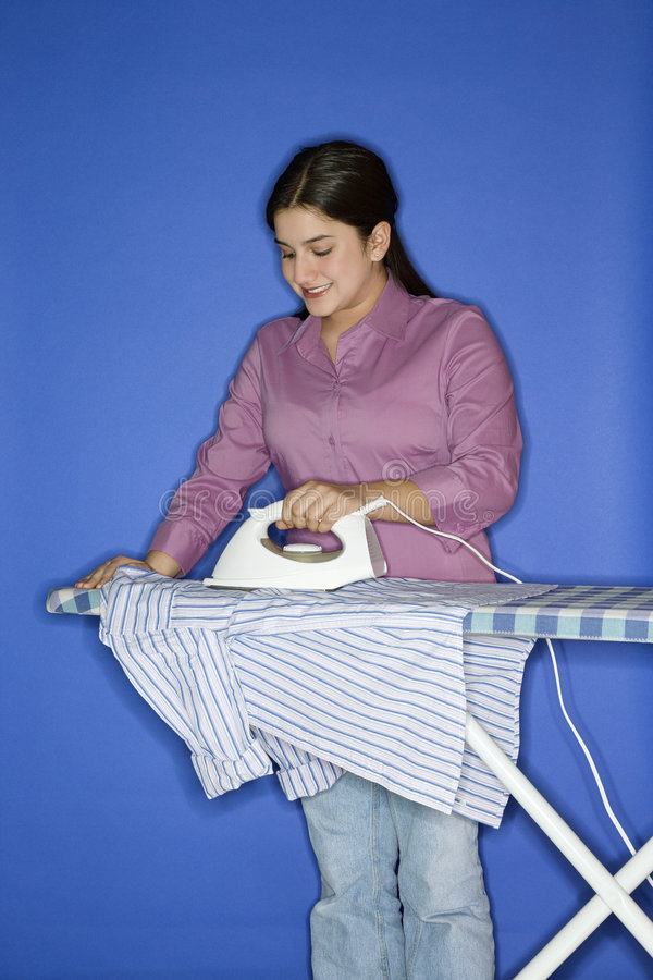 Teen girl ironing shirt. stock photos
