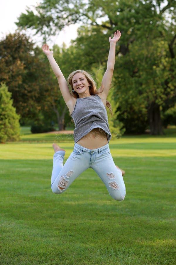 Teen girl jumping stock photography