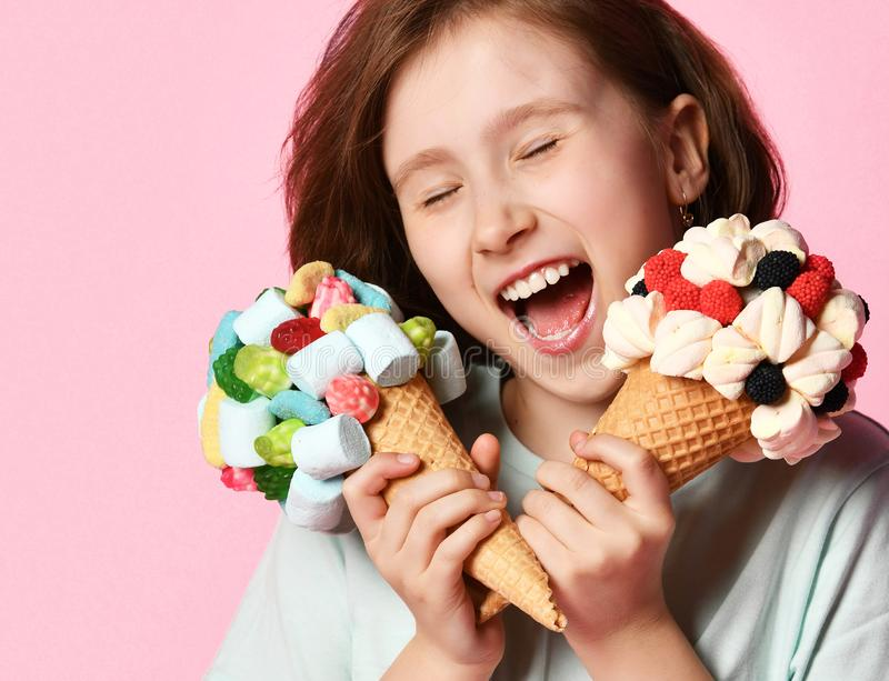 Teen girl kid holds two big ice cream in waffles cone with raspberry marshmallow marmalade and tries to eat lick both on pink royalty free stock images