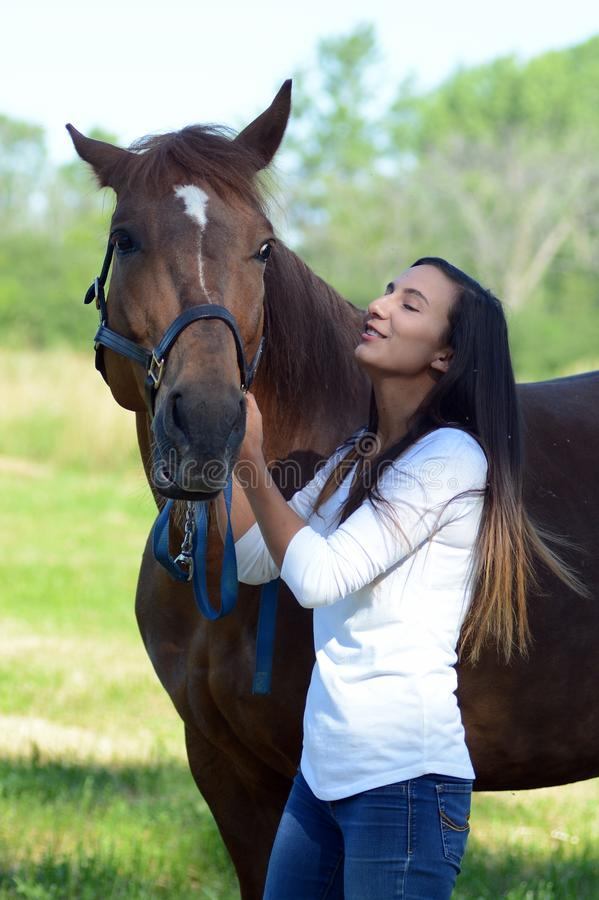 A teen girl laughs with her horse stock image