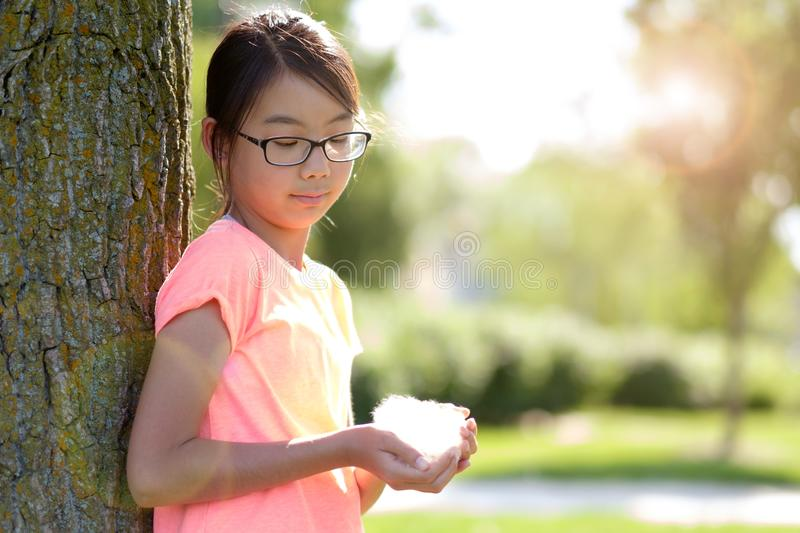 Teen girl leaning against tree in park stock image