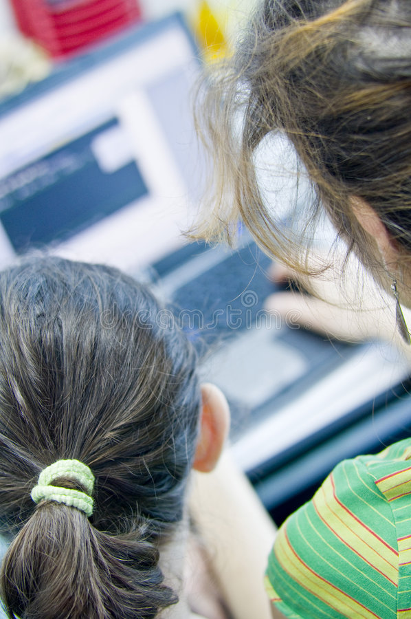 Teen girl learning computers. From her sister stock photography