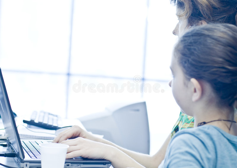 Teen girl learning computers. From her sister royalty free stock photos