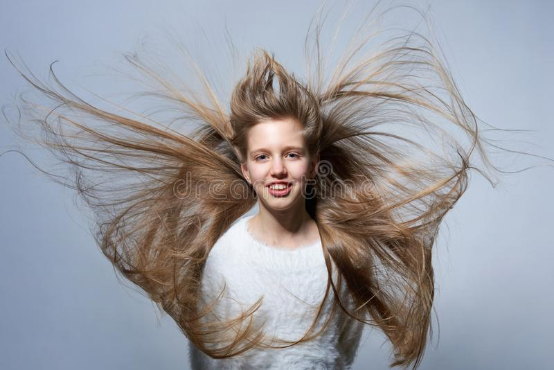 Teen girl with long hair flying in air. Over studio grey background royalty free stock photo