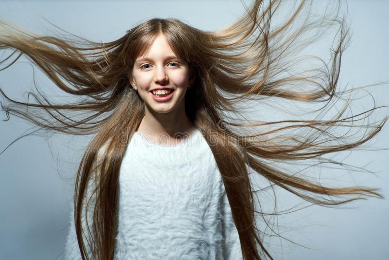 Teen girl with long hair flying in air. Over studio grey background stock images