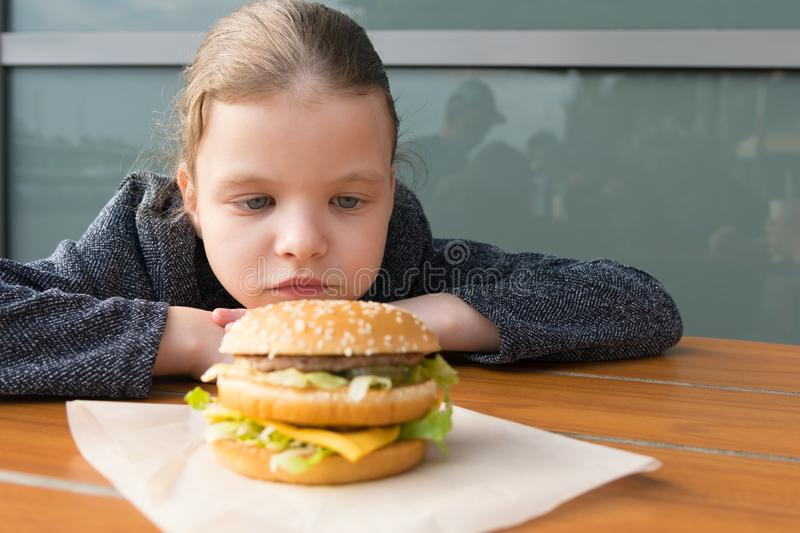 Teen girl looking at appetizing Burger lying in front of her on the table royalty free stock photos