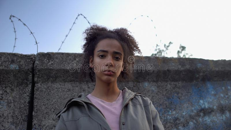 Teen girl looking at camera, dreaming to escape prison, juvenile delinquency. Stock photo royalty free stock photo