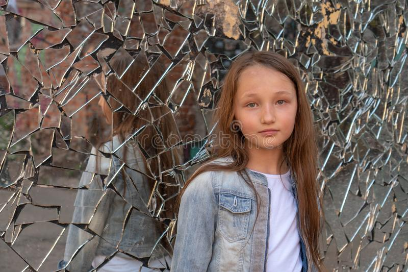 Teen girl looking at the camera. Reflection in a broken mirror. about the problems of adolescents. Transitional age.  royalty free stock image