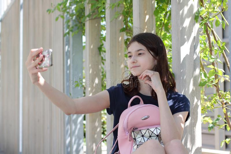 Teen girl makes selfie by mobile phone. Portrait of a girl with a backpack on a wooden bench in the park. stock photos
