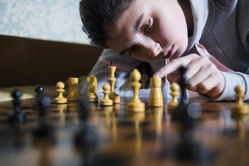 Teen girl making checkmate playing chess. She is winner stock image