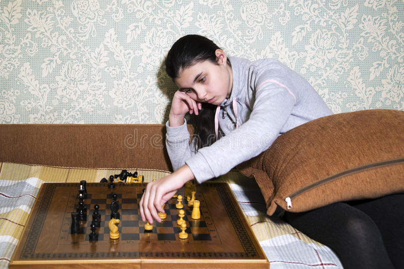Teen girl making checkmate playing chess. She is winner royalty free stock photography