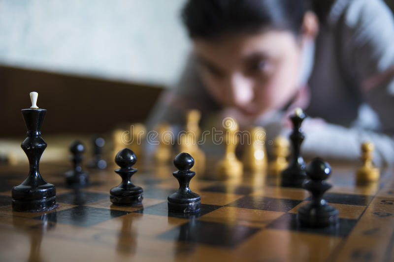 Teen girl making checkmate playing chess. She is winner royalty free stock images