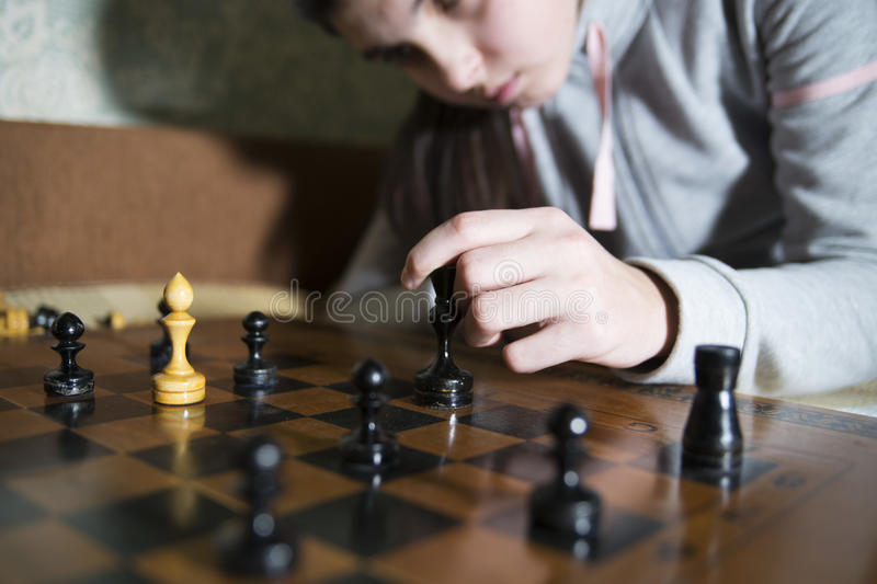 Teen girl making checkmate playing chess. She is winner royalty free stock photo